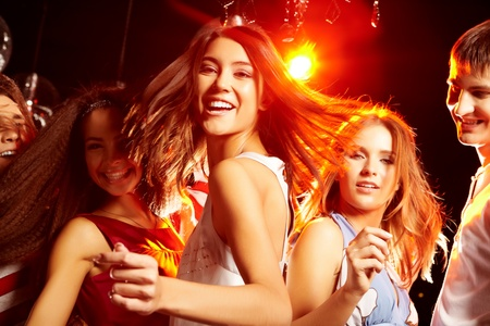 surrounded: Pretty clubber dancing surrounded by her friends and looking at camera with smile