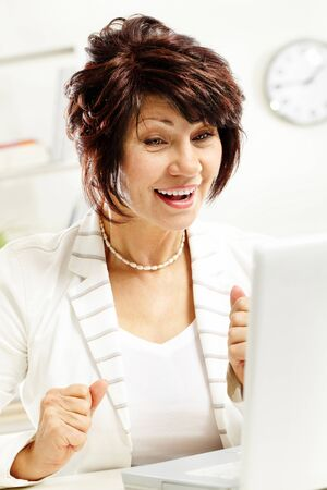 Portrait of amazed middle-aged female looking at laptop display photo