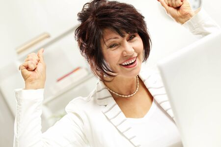 winning woman: Portrait of amazed middle-aged female looking at laptop display Stock Photo