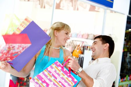 Joyful man and woman with bags looking at each other in the department store photo