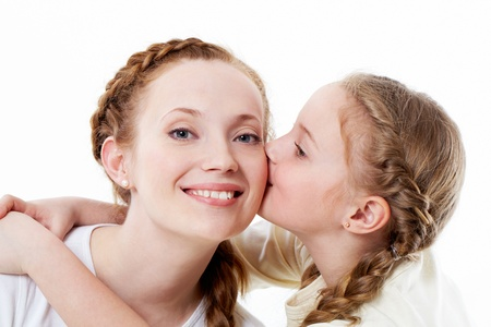 Portrait of pretty girl kissing her mother photo