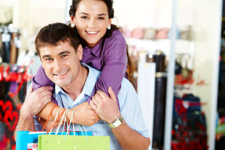 Pretty woman embracing happy man in the department store photo
