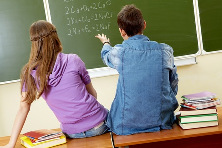 Back view of guy pointing at blackboard while explaining formula to girl photo