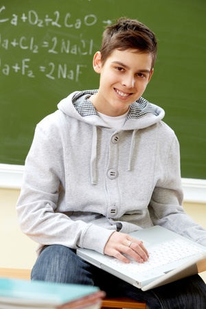 Portrait of smart lad with laptop looking at camera Stock Photo - 9725559