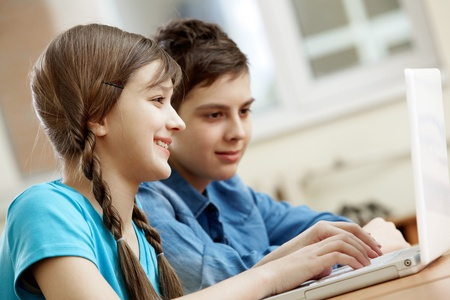 Portrait of teenage girl typing with her classmate at background photo