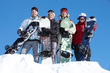 Portrait of happy company of guys and girl with snowboards photo