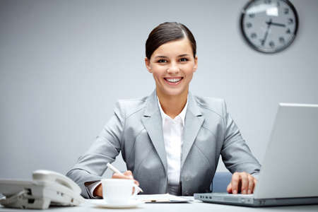 women working: Image of young employer looking at camera while planning work in office Stock Photo