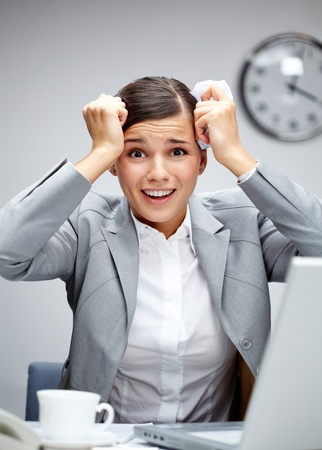 stressed woman: Image of shocked employer touching her head at workplace