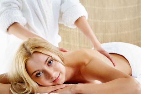 Portrait of calm female looking at camera during procedure of massage photo