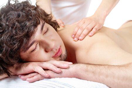 Portrait of calm guy enjoying the procedure of massage photo