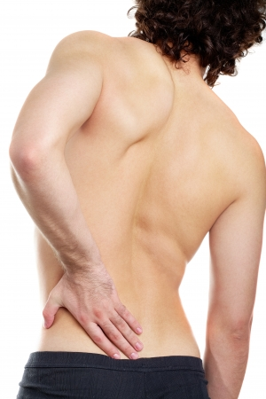 aching muscles: Back view of young man touching aching back