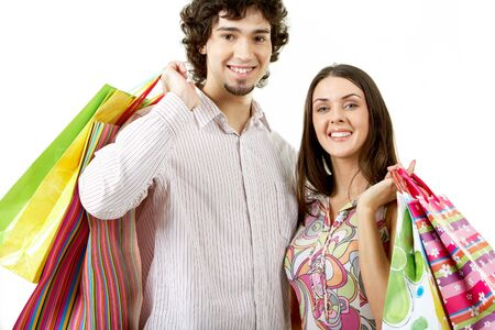 Portrait of happy couple holding bags in hands photo