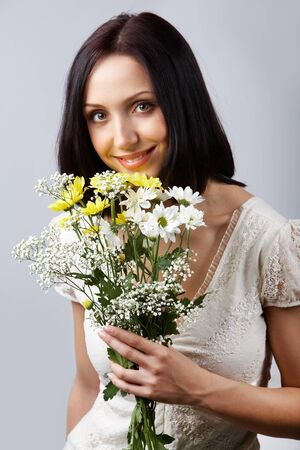 Portrait of pretty girl with bunch of chrysanthemums looking at camera photo