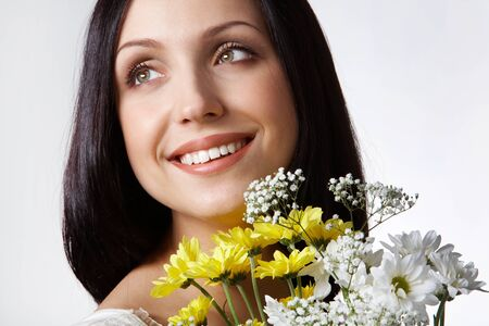 Portrait of pretty girl with bunch of chrysanthemums on grey background photo