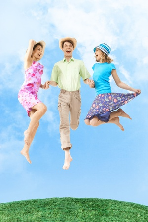 Portrait of joyful girls in jump holding happy man by hands with blue sky on background photo