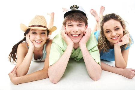Portrait of three happy friends lying and looking at camera in isolation photo
