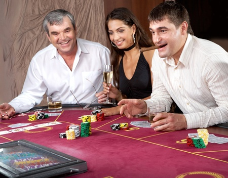 Portrait of people sitting at the table and gambling photo