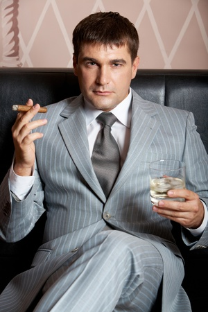 Portrait of handsome man in grey suit sitting on leather sofa with whisky and cigar in casino photo