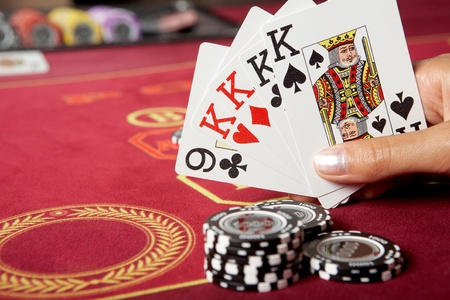 Image of five game cards in hands with black chips near by