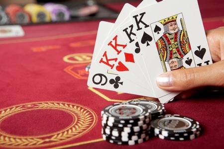 fichas de casino: Imagen de cinco tarjetas de juego en manos con chips negros cerca de  Foto de archivo