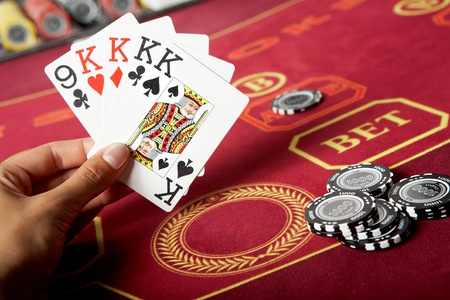 Image of five game cards in hands with black chips near by  photo