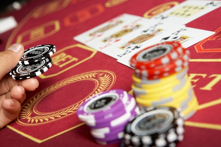 casino table: Image of black chips in hand over casino table