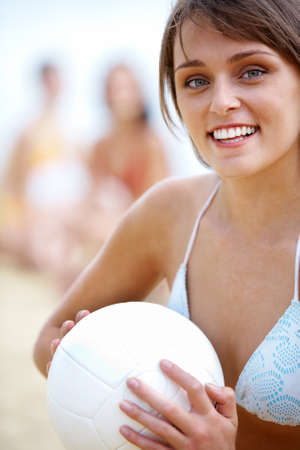 Portrait of fresh woman with ball looking at camera on summer vacations photo