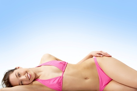 lying on the stomach: Image of pretty female in pink bikini posing in front of camera
