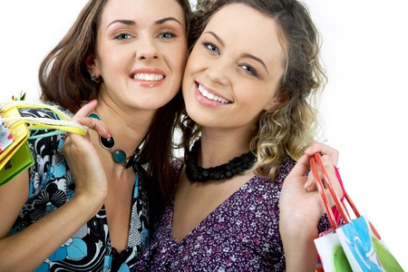 Portrait of cheerful girls carrying shopping bags and looking at camera happily photo