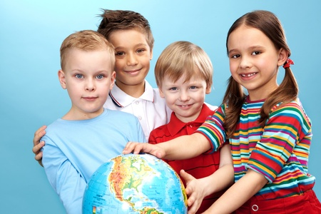 Group of adorable boys and girl with globe photo