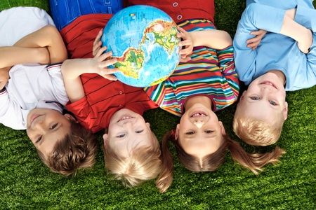 holding globe: Gruppo di bambini felici sdraiato su un erba verde con globo Archivio Fotografico