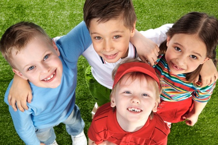 Group of happy children on green grass looking at camera Stock Photo - 9725886