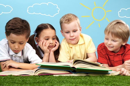child book: Group of happy children lying on a green grass and reading books