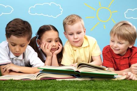 ni�os leyendo: Grupo de ni�os felices en un c�sped verde y lectura de libros
