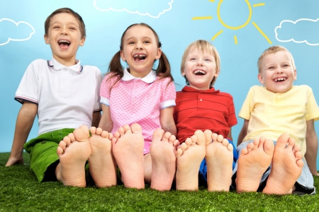 barefoot people: Group of happy children lying on a green grass