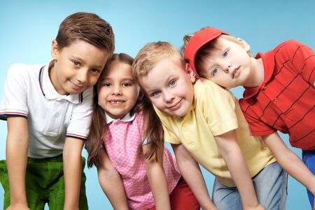 happy kids: Group of adorable kids looking at camera on blue background Stock Photo