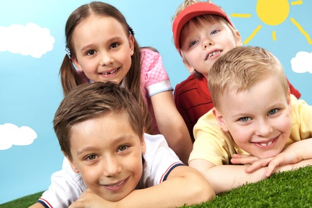 Group of happy children lying on a green grass Stock Photo - 9725857