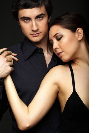 Portrait of elegant girl with handsome man looking at camera on black background Stock Photo - 9725891