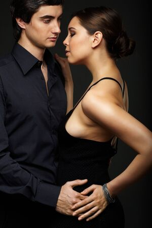 passionate embrace: Portrait of elegant couple on black background