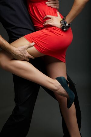 Man holds leg of female in red dress and high-heeled shoes photo