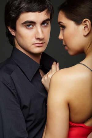 Portrait of handsome man looking at camera with beautiful woman near by photo