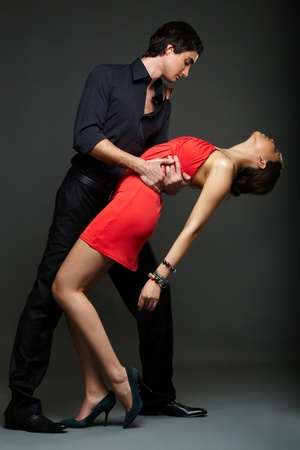 Portrait of elegant couple dancing on black background photo