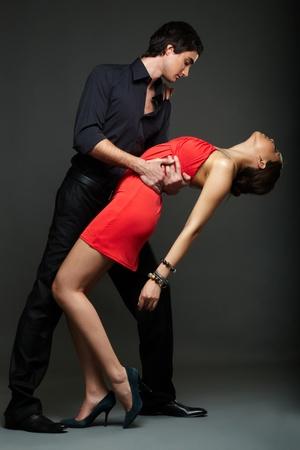 elegant couple: Portrait of elegant couple dancing on black background