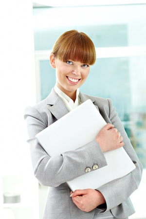 Portrait of cheerful girl holding laptop and looking at camera photo