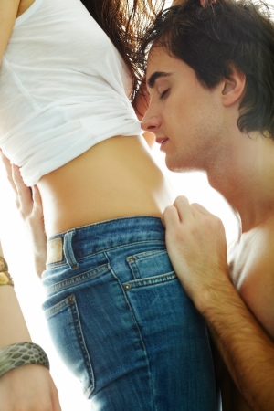 seductive couple: Portrait of young man face by his girlfriend�s belly