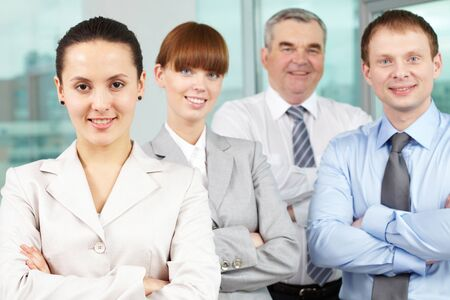 Portrait of friendly leader looking at camera with three employees behind Stock Photo - 9725750