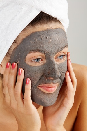 purifying: Beautiful woman with purifying facial mask keeping her palms by her face