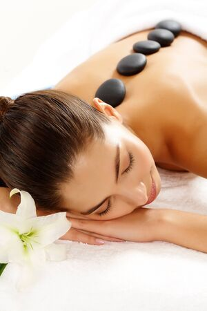 Portrait of young female with spa stones on back having massage photo