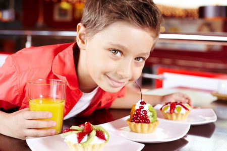 Portrait of cute lad with glass of juice and tasty cupcakes in cafe Stock Photo - 9725811