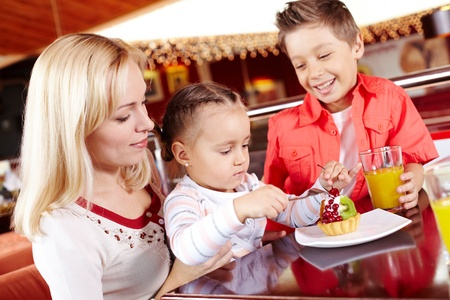 Portrait of cute girl eating cupcake with her mother and brother near by in cafe Stock Photo - 9725825